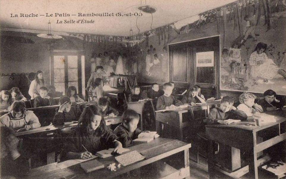 Carte postale éditée par l'imprimerie de la Ruche de Rambouillet : les enfants sont dans la salle de classe unique de l'école.